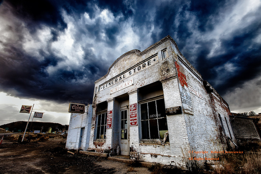 Raging Storm Clouds of Time (B&W&C):  A wind storm thrusts clouds aggressively across the sky, passing a once vibrant general store without notice and relegating it to a meaningless, forgotten history, Eureka Nevada, USA.
