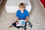 Portrait of a blond boy sitting near sofa doing homework