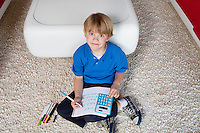 Portrait of a blond boy sitting near sofa doing homework