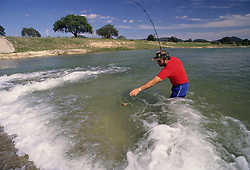Stock photo of a man standing in the middle of a Texas river fishing