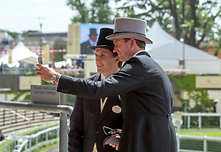 © Licensed to London News Pictures. 17/06/2014. Ascot, UK .  Two men take a selfie. Day one at Royal Ascot 17th June 2014. Royal Ascot has established itself as a national institution and the centrepiece of the British social calendar as well as being a stage for the best racehorses in the world. Photo credit : Stephen Simpson/LNP
