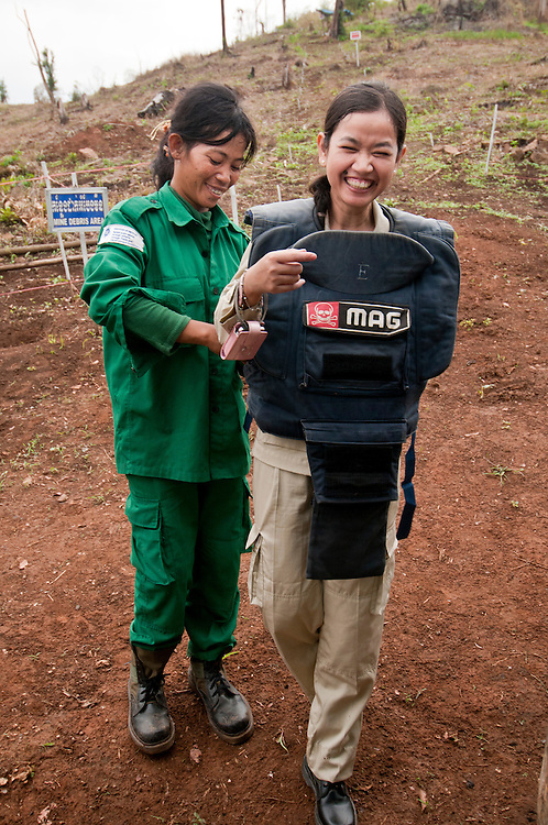 "Sokhon helps her friend, Yean Maly, put on body armor in a safe zone at the MAG base camp before entering the "".Koun Phnum"" or ""Baby Mountain"" minefield...Kheun Sokhon, age 29, is a female deminer for Mines Advisory Group (MAG), in Palin Province, Cambodia.  She searches for land mines - facing the same threat that shattered her life at age 19 - when she stepped on a mine.  She admits, ""I don't want people to experience what I have been through."" ......Back in 2006, in a moment of sadness she told her friend, Yean Maly, ""I never want to get married again. I don't think any man could truly love an amputee woman like me.""...."