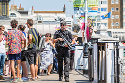 © Licensed to London News Pictures. 01/07/2016. Brighton, UK. Armed Police officers patrol the Brighton Palace Pier as thousands of visitors take top the beach in Brighton and Hove. Photo credit: Hugo Michiels/LNP