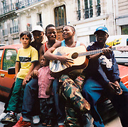 Group of teenagers sitting on a car in Paris one boy playing a guitar