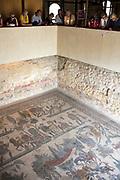 Tourists view famous mosaics and mosiac art of hunting scenes at ancient Roman Villa del Casale, Piazza Armerina, Sicily, Italy