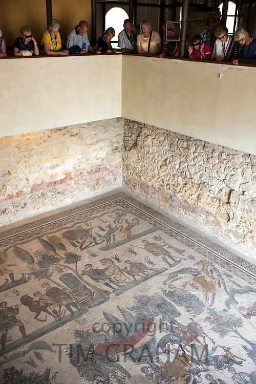 Tourists view famous mosaics and mosiac art of hunting scenes at ancient Roman Villa del Casale, Piazza Armerina, Sicily, Italy