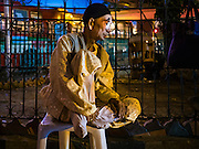 17 FEBRUARY 2016 - BANGKOK, THAILAND:   A performer relaxes backstage before a Chinese opera performance in Bangkok. He's a member of a small troupe that travels from Chinese shrine to Chinese shrine performing for a few nights before going to another shrine. They spend about half the year touring in Thailand and the other half of the year touring in Malaysia. Members of the troupe are paid about 5,000 Thai Baht per month (about $140 US). Chinese opera was once very popular in Thailand, where it is called Ngiew. It is usually performed in the Teochew language. Millions of Chinese emigrated to Thailand (then Siam) in the 18th and 19th centuries and brought their culture with them. Recently the popularity of ngiew has faded as people turn to performances of opera on DVD or movies. There are still as many 30 Chinese opera troupes left in Bangkok and its environs. They are especially busy during Chinese New Year and Chinese holiday when they travel from Chinese temple to Chinese temple performing on stages they put up in streets near the temple, sometimes sleeping on hammocks they sling under their stage. Most of the Chinese operas from Bangkok travel to Malaysia for Ghost Month, leaving just a few to perform in Bangkok.   PHOTO BY JACK KURTZ
