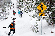 Rear view of four adults walking on a trail in the snow past a yellow street crossing sign in Bend, Oregon. (releasecode: jk_mr1036, jk_mr1032, jk_mr1031, jk_mr1033) (Model Released)