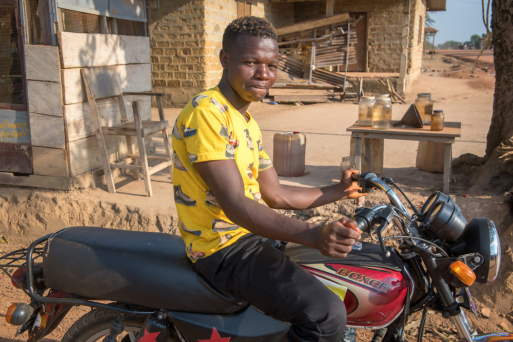 A young man poses on his motorcycle in Ganta, Liberia