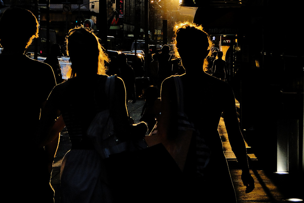 Silhouette of people walking down sun drenched street in nyc. NYC 2009