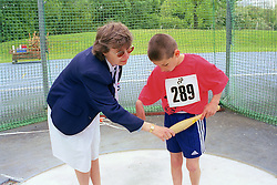Judge assisting young disabled boy taking part in Mini games sports event held at Stoke Mandeville Stadium,
