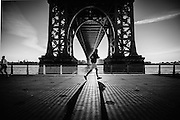 Picture of a jogger passing by the Williamsburg Bridge on the East River Park, NYC