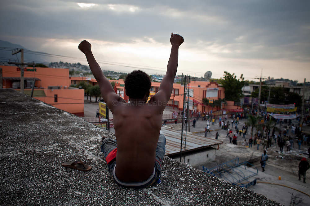 Martelly's supporters demonstrate, in the streets of Port-au-Prince, to protest against the results of the presidential elections and the defeat of their leader, Michel Martelly. /// A Martelly's supporter encourages his friend to fight Minustah's soldiers from a roof of Port-au-Prince.