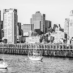 Boston skyline black and white photography with Boston Harbor, downtown Boston skyscrapers, Port of Boston pier and sailboats. Panoramic picture ratio is 1:3.