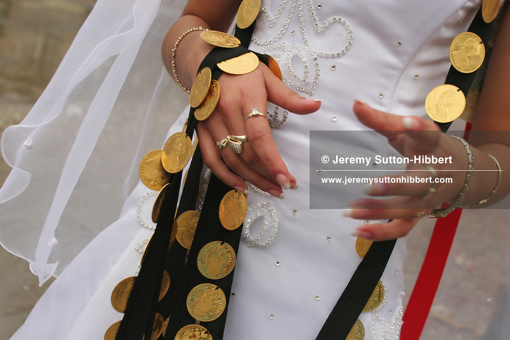 14 year old roma (gypsy) bride Garoafa Mihai walking in the street with her dowry of gold coins, in Sintesti, Romania, on Sunday, Sept. 24th 2006. Day two of the wedding between Garoafa Mihai, aged 14, and Florin 'Ciprian' Lulu, aged 13, Roma (gypsies) from the village of Sintesti,15 kilometres from Bucharest, Romania. Their partnership was decided by their parents and not through love, and under Romanian law is illegal. The children will neither complete legal paperwork for the wedding, nor visit the local Romanian Orthodox church for a blessing. On her wedding day Garoafa wore approximately 30-40,000 USD of gold Franz Josef coins on her dress, part of the large dowry that she takes with her as she begins her married life. For the guests and for the people of the village another 30,000 USD of pigs, approximately 100,  were killed to be eaten and given away as presents of food. Another 30,000 USD was spent on famous Roma musicians to come and sing 'manele'  type music at the wedding extolling the wealth and status of their patrons for the weekend in their songs.