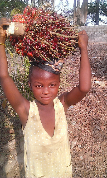 little girl carrying palm nuts