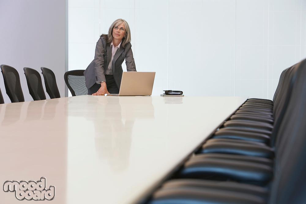 Business woman using laptop in board room