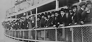 Immigrants arriving at Ellis Island on a ship, photograph, displayed in the Ellis Island Immigration Museum, in the main building on Ellis Island, the immigration processing centre for the United States from 1892 to 1954, at the mouth of the Hudson river in New York City, NY, USA. Ellis Island and its Immigration Museum are part of the Statue of Liberty National Monument and are managed by the National Park Authority. Picture by Manuel Cohen