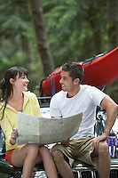 Couple with map sitting on car