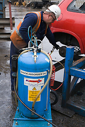 EndofLife vehicle (ELV) operative sucking shock absorber oil from a car to comply with regulations prior to the vehicles being transported to a shredding facility,