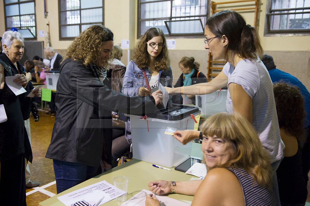 """© Licensed to London News Pictures. 01/10/2017. Barcelona, Spain.  <br /> <br /> One of the first person voting at Sedeta de Gracia´s Centre Civic.<br /> <br /> Students, their parents, associations and neighbours have organized to carry out """"playful activities"""" during the weekend and keep open the Sedeta de Gracia´s Centre Civic.<br />  <br /> Since early in the morning dozens of people wait at the college´s door for the voting time under the rain.<br /> <br /> Mossos d´Escuadra said they won´t do nothing if that can destabilize social order.<br /> <br /> Catalonia is awaiting for today, October 1st, when the Spanish Region wants to vote in a self-determination referendum to get a independence.<br /> <br /> The Referendum´s Law was passed on last September 6th at the Catalonian Parliament thanks to the votes of """"Junts pel Sí"""" and """"CUP"""". Then it was suspended by the Spanish Constitutional Court, on next day.<br /> Carles Puigdemont, the President of the Government ofCatalonia, said he would ignore that and he and his Government will continue with the Referendum.<br /> <br /> The Spanish Government has sent to Catalonia thousands of """"Guardia Civil"""" and """"Policía Nacional"""" officers (two of the Spanish forces and state security forces), to enforce the ruling of the Constitutional Court and avoid the voting process on next Sunday. They will work with the Mossos d´Escuadra (the Autonomic police in Catalonia).<br /> <br /> To avoid the vote, the Spanish Government has prevented the opening of polling stations, some of which are schools.  <br /> <br /> Photo credit: Gustavo Valiente/LNP"""