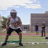 Austin Woods uses an elastic band in a side stepping drill at Miyamura High School in Gallup Monday as a part of the Patriots football practice.