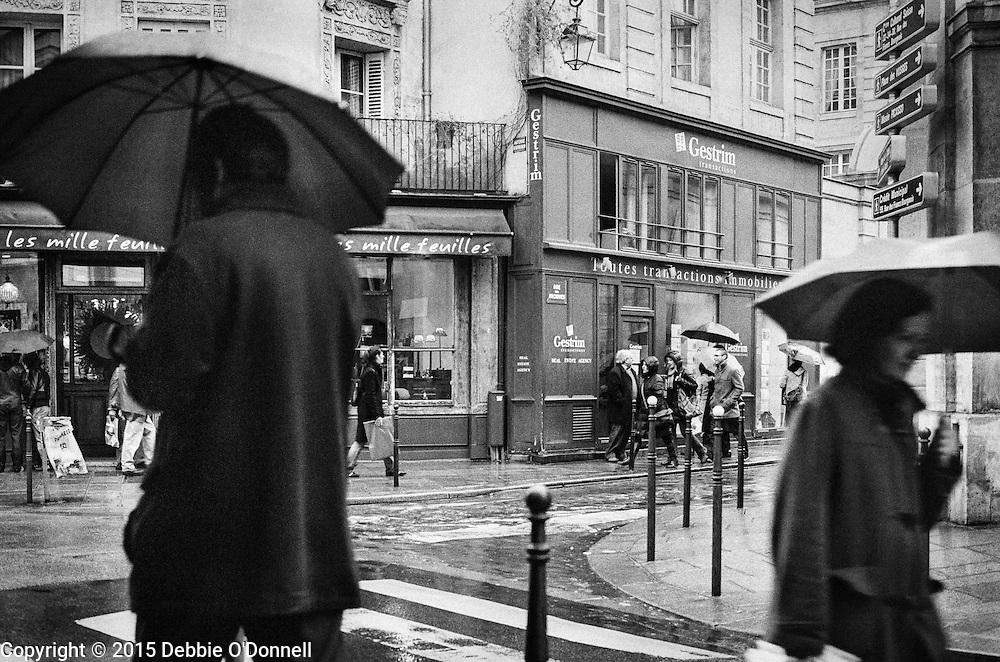 A man and woman holding umbrellas walk by each other while shopping on a rainy day on Rue Rambuteau, Paris.