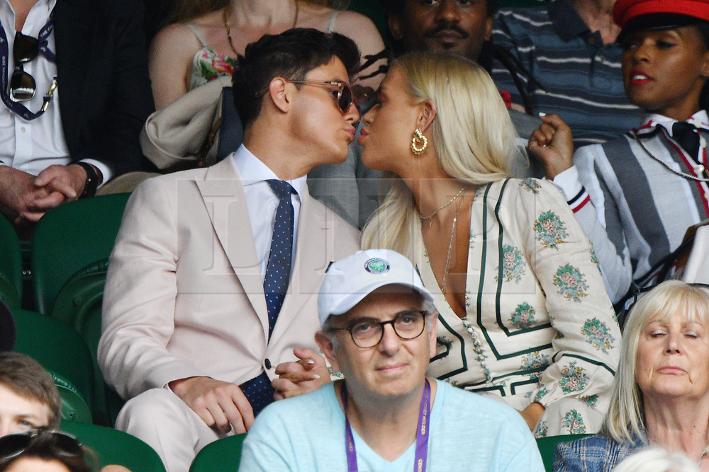 © Licensed to London News Pictures. 01/07/2019. London, UK. Sam Prince and Lottie Tomlinson watch tennis from the centre court at the Wimbledon Tennis Championships 2019 on Day 1 held at the All England Lawn Tennis and Croquet Club. Photo credit: Ray Tang/LNP