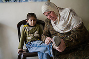 Abdul-Baset Razem's mother-in-law ties a boy's shoelaces at their home in Abu Dis, East Jerusalem, Palestine.  (Abdul-Baset Razem is featured in the book What I Eat: Around the World in 80 Diets.)