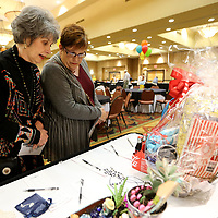 Judy Collier and Marta Bolen, both from Etta, look over items that are up for silent auction during the Le Bonheur Family Affair gathering Monday night at the BancorpSouth Conference Center in Tupelo. Collier and Bolen came to support Alex Robertson. For eight weeks, three families, the Robertsons of Myrtle, the McKinnys fron Nettleton and the Francis family from Nettleton, have been raising money in a friendly competition to benefit Le Bonheur Children's Medical Center. Items were on display for a silent auction would count to the families fundraiaing totals.