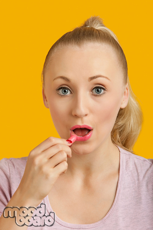 Portrait of beautiful young woman applying lipstick over yellow background