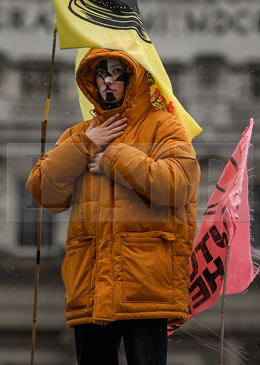 © Licensed to London News Pictures. 07/10/2019. London, UK. An Extinction Rebellion activist stands on a  wooden structure in front of Admiralty Arch in Trafalgar Square,  Westminster. Activists plan to converge on Westminster blockading roads in the area for at least two weeks calling on government departments to 'Tell the Truth' about what they are doing to tackle the Emergency. Photo credit: Ben Cawthra/LNP