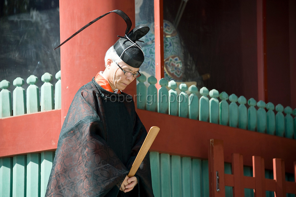 Head priest Shigeho Yoshida stands by the gates of the main hall of Tsurugaoka Hachimangu shrine during the second day of the 3-day Reitaisai grand festival in Kamakura, Japan on  15 Sept. 2012.  Photographer: Robert Gilhooly