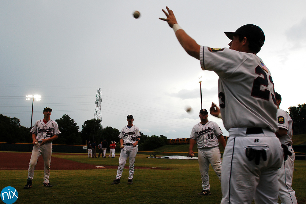 Grayson Thompson (23) and his Kannapolis Post 115 teammates toss baseballs around while waiting during a rain and lightning delay Saturday evening.