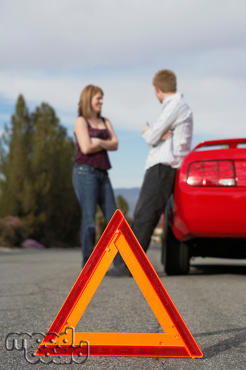 Two motorists standing by broken down car with warning triangle behind it