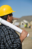 Construction worker holding rolled up blueprint