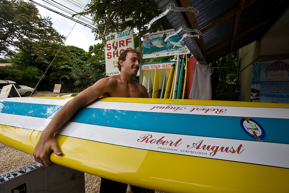 A surfer carries a shiny new Robert August Longboard into a surf shop in Tamarindo, Costa Rica