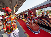 India, Rajasthan. Jaipur station. Maharajas' Express luxury train. Passengers greeted by traditional dance and music group.