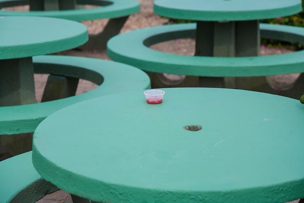 Small round plastic container of red ketchup sits on top of round green table at outdoor restaurant