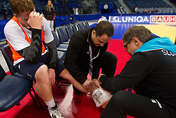 Physiotherapist Sokol Kadrija and Gorazd Zuzek with Matej Gaber of Slovenia (L) who has twisted his ankle during practice session of Slovenia team 1day before handball match against Macedonia for 5th place at 10th EHF European Handball Championship Serbia 2012, on January 26, 2012 in Beogradska Arena, Belgrade, Serbia.  (Photo By Vid Ponikvar / Sportida.com)