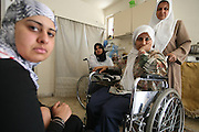 Iraqi refugees  Ameer Ibrahim with her three daughters Warka'a 30, (white head scarf) and her sister Arwa'a ,32, are both confined to wheel chairs and their sister   Wala who also is unable to walk on her own at their rented apartment in Amman, Jordan July 30,2007. The women fled their war torn home in Baghdad, Iraq one year ago . The sisters started to suffer neurological damage after coalition forces t in 1991 bombed Iraqi bunkers nearby their home when family was living in Tikrit, Iraq . The family claims that the medical doctors who have treated them believe  their disablities were caused by the  gas following the bombings.  (Photo by Heidi Levine/Sipa Press).