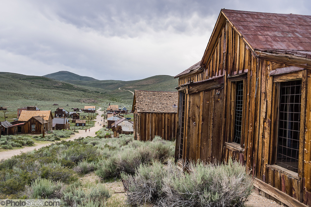 "Ramshackle houses line Green Street in Bodie, California's official state gold rush ghost town. Bodie State Historic Park lies in the Bodie Hills east of the Sierra Nevada mountain range in Mono County, near Bridgeport, California, USA. After W. S. Bodey's original gold discovery in 1859, profitable gold ore discoveries in 1876 and 1878 transformed ""Bodie"" from an isolated mining camp to a Wild West boomtown. By 1879, Bodie had a population of 5000-7000 people with 2000 buildings. At its peak, 65 saloons lined Main Street, which was a mile long. Bodie declined rapidly 1912-1917 and the last mine closed in 1942. Bodie became a National Historic Landmark in 1961 and Bodie State Historic Park in 1962."