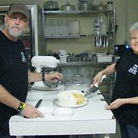 ALICE ORTIZ/BUY AT PHOTOS.MONROECOUNTYJOURNAL.COM<br /> Frank and Glenda Adams cut a slice of Tropical Paradise Cake for a customer at their restaurant, Adams Family Restaurant.