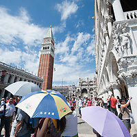 VENICE, ITALY - AUGUST 11:  Tourists que in  St Mark's Square for the entrance to the Basilica on August 11, 2011 in Venice, Italy. Italian heritage group Italia Nostra warned  that Venice is facing an irreversible environmental catastrophe unless visitor numbers are capped. The acceptable maximum number of tourists for Venice is 33,000. In 2011 the average number of visitors to the city daily is 60,000 that is too high for such a fragile city and is causing the gradual destruction of the lagoon ecosystem.