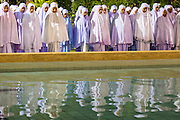 11 JULY 2013 - PATTANI, PATTANI, THAILAND:  Women pray behind the reflecting pool and fountain at Pattani Central Mosque in Pattani, Thailand, Thursday night for Ramadan services. The mosque is one of the busiest in south Thailand. About 15,000 people attend nightly Ramadan services in the mosque. Ramadan is the ninth month of the Islamic calendar, and the month in which Muslims believe the Quran was revealed. Muslims believe that the Quran was sent down during this month, thus being prepared for gradual revelation by Jibraeel (Gabriel) to the Prophet Muhammad. The month is spent by Muslims fasting during the daylight hours from dawn to sunset. Fasting during the month of Ramadan is one of the Five Pillars of Islam.     PHOTO BY JACK KURTZ