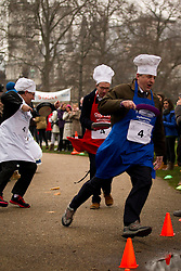 © Licensed to London News Pictures. 12/02/2013. London, UK. Lord Redesdale (R), Liberal Democrat MP Martin Horwood (L) and Patrick Wintour of the Guardian (R) toss pancakes as they take part in the annual Rehab Parliamentary Pancake Race in Westminster, London today (12/02/2013).The race involving MPs from the House of Commons, Lords from the House of Lords and members of the Parliamentary Press Gallery, is aimed at raising awareness for the Rehab; a charity that works to support people with disabilities, takes place every year in Victoria Tower Gardens next to Parliament and was won this year by the House of Commons team. Photo credit: Matt Cetti-Roberts/LNP