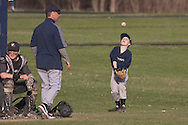Goshen, New York - A young boy, at right, tosses and catches a ball as John S. Burke Catholic plays Fallsburg in a a varsity baseball game on April 21, 2014.