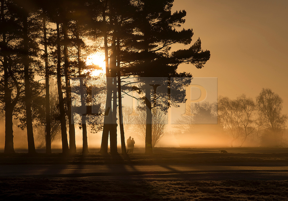 © Licensed to London News Pictures. 16/02/2016. Walton Heath, UK. People walk their dogs at sunrise near Walton Heath golf course.  Temperatures locally were as low as -5 centigrade. Photo credit: Peter Macdiarmid/LNP