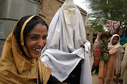 Mukhtar Mai, 33, is teased by a family member wearing a burqa, which Mai now refuses to wear, Meerwala, Pakistan, April 28, 2005.<br />