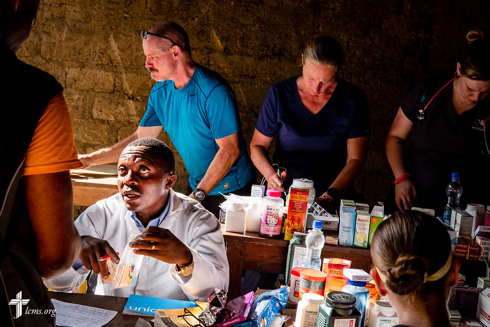 Francis Lahai, a pharmacist from Sierra Leone, dispenses prescriptions to patientson the first day of the LCMS Mercy Medical Team on Monday, May 7, 2018, in the Yardu village outside Koidu, Sierra Leone, West Africa. Behind him is the Rev. Gary Schulte, area director for West and Central Africa, Stephanie Schulte, fellow career missionary, and nurse Lauren Awe from La Vista, Neb. LCMS Communications/Erik M. Lunsford